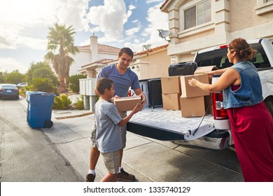hispanic family unloading pickup truck and moving into new house in las vegas