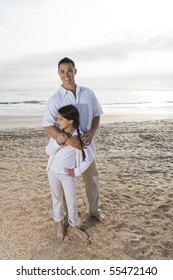 Hispanic father and 9 year old daughter standing together on beach