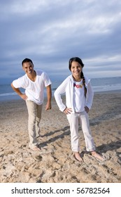Hispanic father and 9 year old daughter having fun on beach smiling at camera