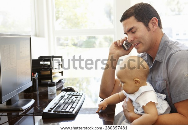 Hispanic father with baby working in home office