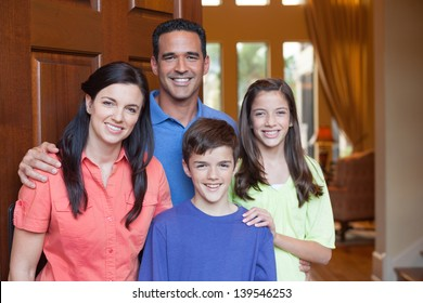 Hispanic father, Caucasian mother and mixed ethnicity son and daughter standing in entryway beside large wooden door of large home, living room with tall windows in background
