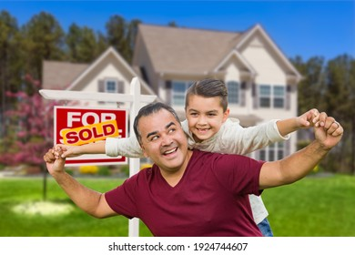 Hispanic Father and Mixed Race Son Having Fun In Front of House and Sold Real Estate Sign.
