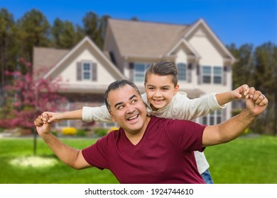 Hispanic Father and Mixed Race Son Having Fun In Front of House.