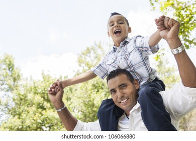 Hispanic Father and Son Having Fun Together Riding on Dad's Back in the Park.