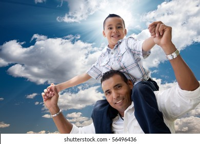 Hispanic Father and Son Having Fun Over Clouds and Blue Sky with Sun Rays.