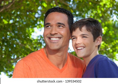 Hispanic father and teenage son happily standing together outside in yard, looking off into distance.