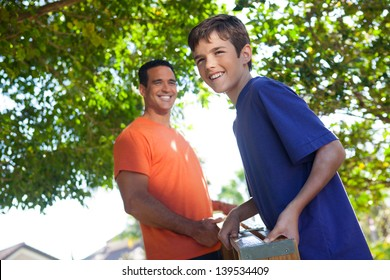 Hispanic father and teenaged son happily carry ladder together outside in yard.