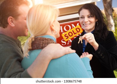 Hispanic Female Real Estate Agent Handing Over New House Keys to Happy Couple In Front of Sold For Sale Real Estate Sign.