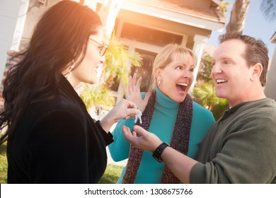 Hispanic Female Real Estate Agent Handing Over New House Keys to Happy Couple In Front of House.