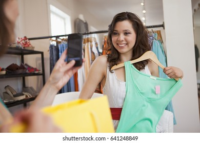 Hispanic friends shopping in clothing store