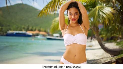 A Hispanic girl acts seductively on the beach