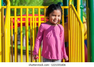A hispanic girl with a pink long sleeve shirt standing in a kids playground with a cute smile on her face.