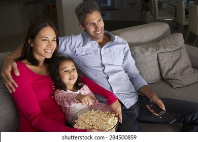 Hispanic Girl Sitting On Sofa And Watching TV With Parents