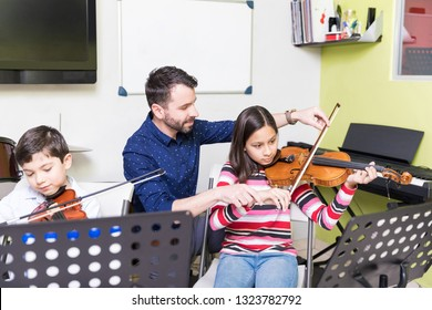 Hispanic girl taking training of playing violin from male teacher in school
