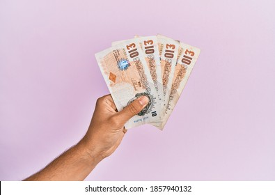 Hispanic hand holding 10 uk pounds banknotes over isolated pink background.