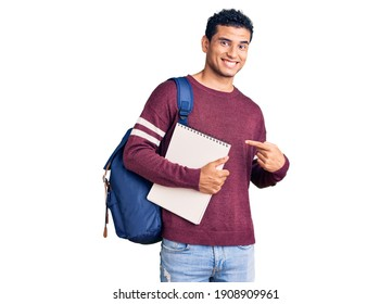Hispanic handsome young man wearing student backpack and notebook smiling happy pointing with hand and finger