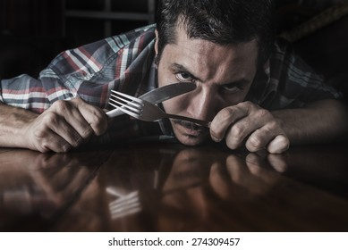 Hispanic hungry man with cutlery in the hands