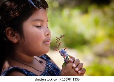 Hispanic little girl with her eyes closed and holding a bouquet of fresh wildflowers to her nose, enjoying the sweet fragrance of the plants.