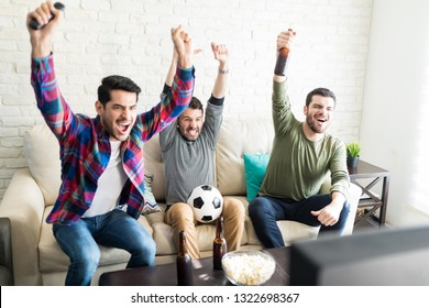 Hispanic male buddies celebrating goal and screaming in front of television at home