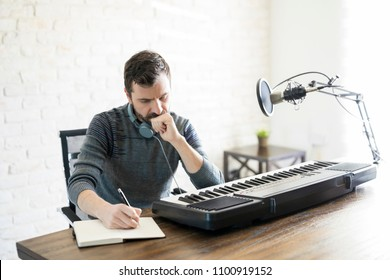Hispanic male songwriter thinking while writing new song in his book
