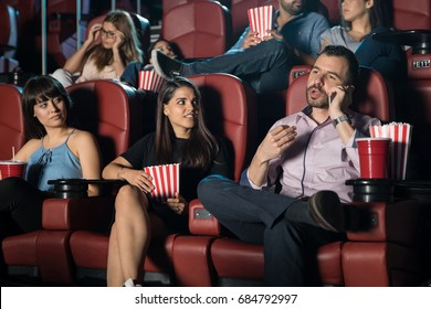 Hispanic man being disrespectful by talking on the phone at the movie theater next to some annoyed neighbors