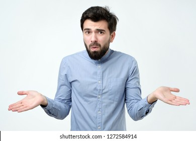 Hispanic man in blue shirt throws up his hands in disbelief