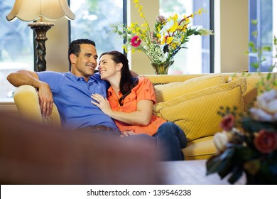 A hispanic man and a caucasian woman in jeans sit on a yellow couch cuddling in their living room with her looking up at him.
