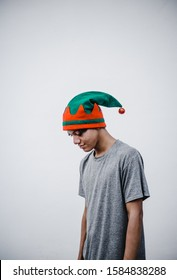 Hispanic man with Christmas hat with his head down. White wall of a street.