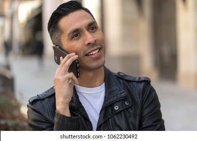 Hispanic man in city talking on cell phone