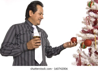A Hispanic man in a dress shirt and tie, holding a drink, while looking at a decorated Christmas tree.
