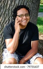 Hispanic man happy as he talks on his smart phone