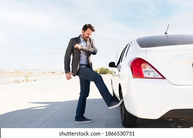Hispanic man in his 30s looking angry and kicking the car's tire because of mechanical problems on the highway