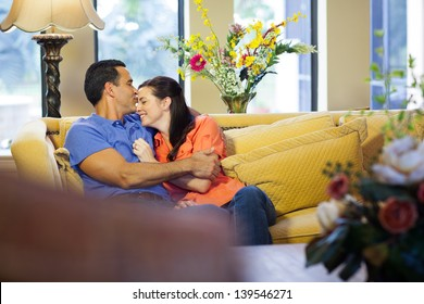 A hispanic man kisses  caucasian woman on her forehead wearing jeans and sitting on a yellow couch in their living room.