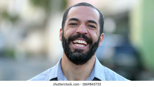 Hispanic man smiling at camera standing outside in street. South American person portrait smile