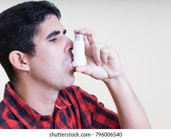 Hispanic man using an inhaler