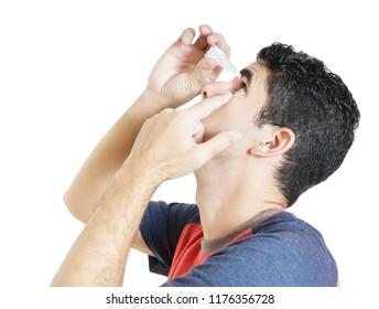 Hispanic man using medication for his eyes isolated on white.