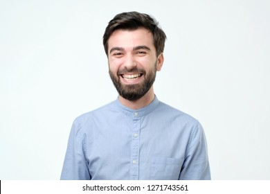 Hispanic man wearing blue shirt laughing or grinning having cheerful look.