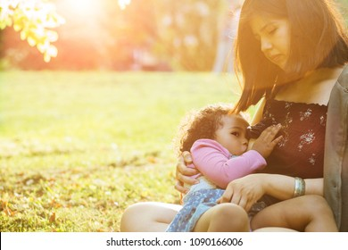 Hispanic mexican mother breastfeeding a dark-skinned mixed race toddler three year old daughter sitting on the green grass in nature - maternity concept. Little hispanic girl looking up. Copy space