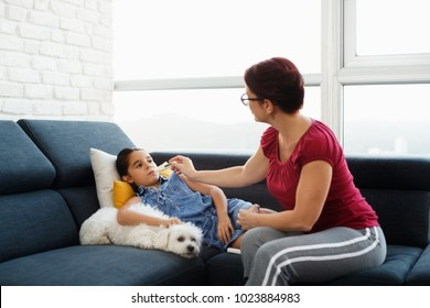 Hispanic mom measuring fever to sick daughter with digital thermometer. Family life at home with latina woman taking care of ill little girl. Health care with mother and child, people and medicine