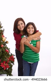 Hispanic mother and daughter isolated on white.