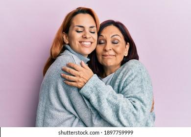 Hispanische Mutter und Tochter lächeln glücklich und umarmt auf isoliertem rosafarbenem Hintergrund.