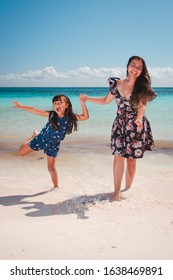 Hispanic mother and her daugther having a fun time togheter at the beach