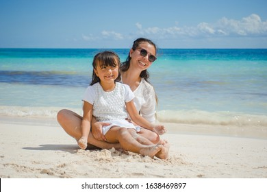 Hispanic mother and her daugther having fun at a Caribbean beach in Playa del Carmen, Mexico.