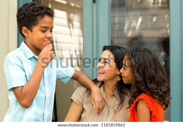 Hispanic mother talking with her children.