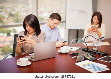Hispanic people in a meeting room ignoring their work and doing some social networking on their smartphones