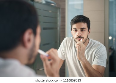 Hispanic person with beard grooming in bathroom at home for morning routine and body care. White metrosexual man brushing teeth in front of mirror