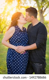 Hispanic Pregnant Young Couple Portrait Outdoors.