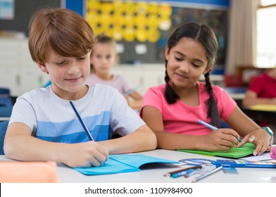 Hispanic school girl looking in boy's book while writing. Elementary children in classroom writing exam while girl copy from classmate. Portrait of cute girl and boy taking notes during lesson.