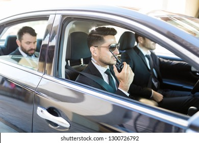 Hispanic security person using radio transceiver while transporting businessman in car