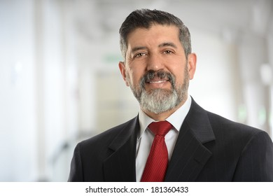 Hispanic senior businessman smiling inside business building
